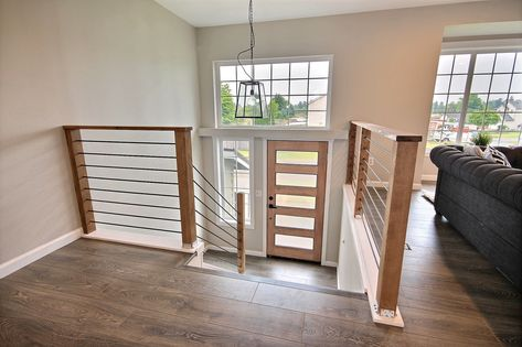 Open concept stair railing created for split level home. Metal stair railing with steel rods and wood posts. Split Level Entryway, Split Foyer, Split Level Home, Split Entry Remodel, Split Level Remodel, Home Renovation, Home Remodeling, Bathroom Remodeling, Bi Level Homes