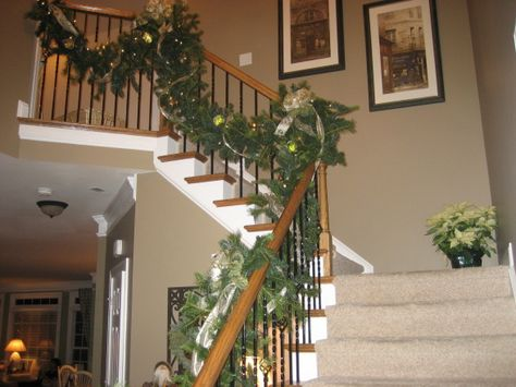 Decorating front stairwell with poinsettia on the landing.