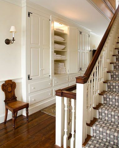Farmhouse living - main hall with linen storage and staircase to second floor.