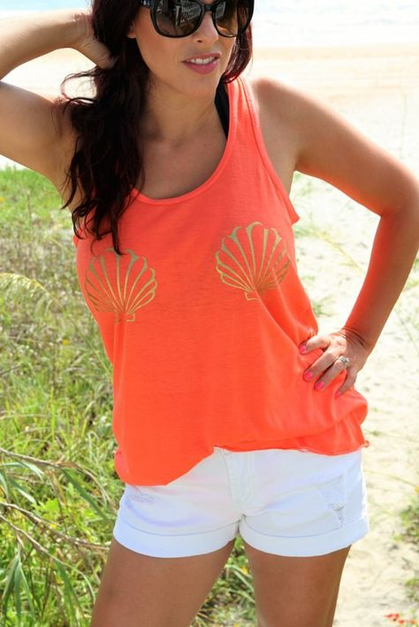 "Say hello to the the beach with a coral women's flowy racer back tank with a gold ""seashells"" print. Perfect to wear over your swimsuit! Printed on 65% poly 35% viscose, 30 single 3.7 oz tank. Extreme"