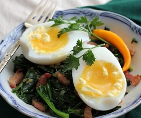 Goose egg with wilted spinach and lardons.
