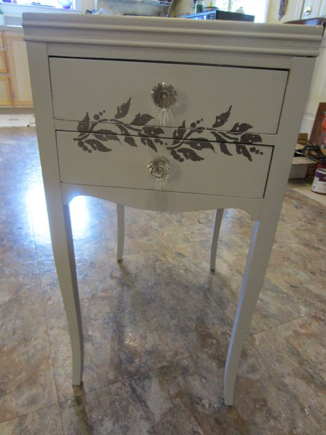 Painted and stenciled end table. This was painted white, tattered and with pink flower knobs.   I painted it a very light gray (latex) and stenciled on leaves with metallic paint.  New glass knobs.