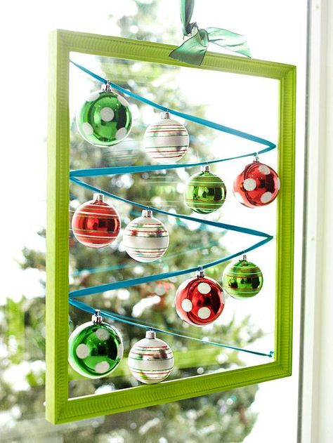 Create a hanging window display with a picture frame, ribbon, and ornaments.