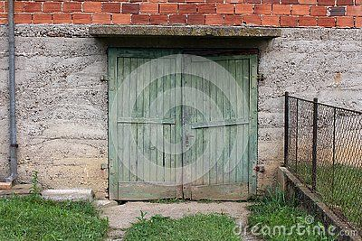 Broken Green Wooden Garage Doors With Rusted Metal Hinges And Small Door Handle Mounted On Concrete Wall Of R Red Brick House Concrete Wall Wooden Garage Doors