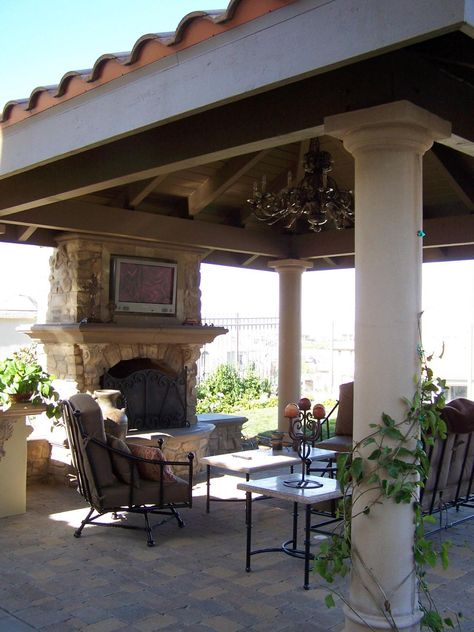 This Mediterranean-style covered patio was designed for optimal outdoor living. It features a stone fireplace with an integrated TV, a spacious seating area and an ornate chandelier.