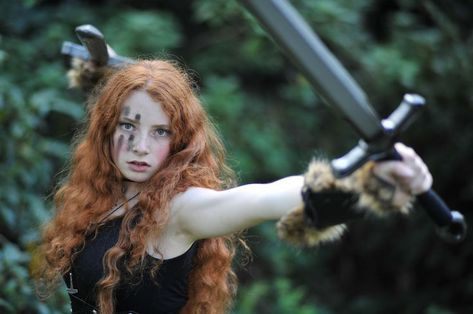 fuckyeahwarriorwomen: [ Image: A photo of a pale skinned woman with curly red hair, dirty fingermarks streaked down her face. She wears a balck tank top and fur-lined vambraces as she wields a pair of swords.