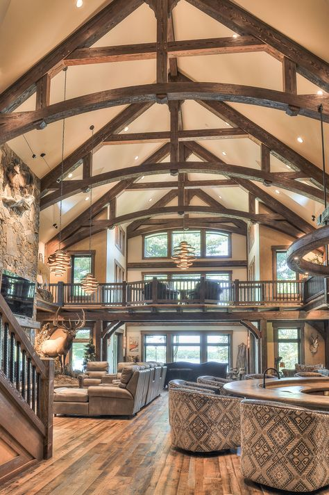 Timber Frame Lake House Arched King Post Trusses with a dark stain give this great room the cathedral ceiling and high windows that give it it's wide open concept feel. Photo courtesy of Shultz Building.