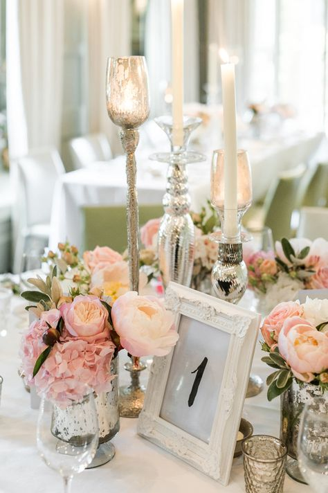 Selection of flowers including peonies, hydrangeas and roses in mercury glass votives, as well as single candlesticks to add a bit of height -  Image by  Ann-Kathrin Koch Photography - A wedding at Barnsley House with the bride in Suzanne Neville. A peony bouquet and white and blush colour theme. Mercury votive table decorations and white pom poms. Photography by Ann-Kathrin Koch.
