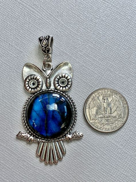 """""""This nature-inspired pendant features a gorgeous labradorite cabochon that shimmers with a glistening aqua blue and royal blue flash. Nestled in a silver-finished frame in the belly of an owl, this simple talisman pendant is perfect for people who love blue and the symbolism of the owl. Owls have long been associated with wisdom, intuition, mystery and unforeseen insight. May this talisman make you smile and dream big in equal measure. Composed of a zinc alloy that is both lead-free and nickel-"""