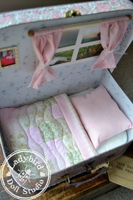 Adorable doll bed made out of a lunchbox styled carrying case. Matilda case 2 by Ladybird Doll Studio. My daughter loves dolls as much as she loves her dinosaurs, cars and blocks. She's a great kid, and things in boxes tickle her fancy. Cute idea for a d