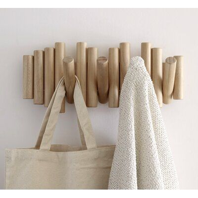 Add a touch of the seaside to your home with this Umbra Picket Rail Hook, Natural. Crafted from bevelled pine wood dowels; you get five functional, flip-down hooks and wall art in one! Holding a weight of 5 lbs each; these multiple natural hooks are easy