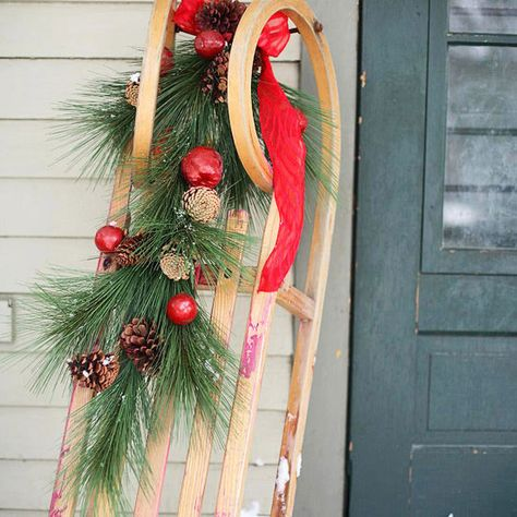 When not cruising the snow-covered hills, an old sled embellished with pine sprigs, pinecones, and fruit does double duty as a welcoming Christmas decoration next to the front door! http://www.bhg.com/christmas/outdoor-decorations/outdoor-holiday-decorating-ideas/?socsrc=bhgpin122014snowysleddisplay&page=20