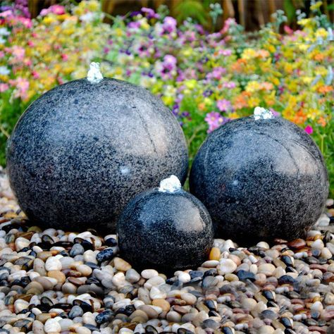 A trio of solid, black granite polished spheres with white LED lights. This feature should not be mistaken for a hollow terrazzo reproduction as it is produced from solid granite and will therefore last for years to come. The included piping, pump and