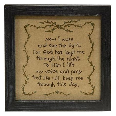 """Now I Wake Prayer Sampler is a primitive stitchery that features a prayer design that is surrounded by a border of vines. Piece includes a black wooden frame that can be hung on a sawtooth hanger or converted and displayed tabletop, with a glass front to protect the fabric. Measures 8¼"""" high by 8¼"""" wide and ¾"""" deep."""