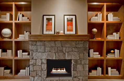 Custom floor to ceiling wood shelving and a stone faced, wood burning, fireplace. Bellevue, WA Coldwell Banker BAIN $3,385,000
