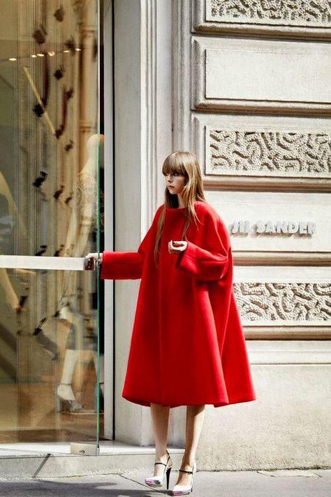 Edie Campbell wearing red wool swing coat and metallic high heels by Jil Sander.