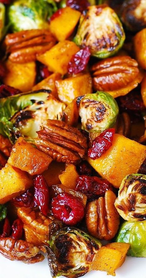 Roasted Butternut Squash and Brussels sprouts with Pecans and Cranberries is one of the best holiday side dishes you'll ever try!  This side dish is packed with vegetables and nuts. It's healthy, gluten-free, vegetarian, and rich in fiber! #butternutsquash #brusselssprouts #salad #sidedish #butternutsquashsalad #brusselssproutssalad #healthy #glutenfree #healthysalad