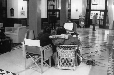 Actor Jack Nicholson and Director Stanley Kubrick review material on a video monitor on the Lobby set of The Shining. Actor Scatman Crothers (or his stand-in) stands in the background.