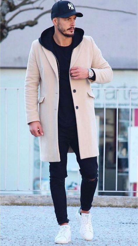 27 Really cool outfits! Stylish men's/unisex winter look — long city coat in tan with baseball cap, dark jeans and dark hoodie with classic crisp white sneakers that balance out white logo on cap