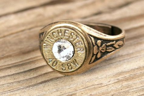 Our 40 Caliber Antiqued Brass Bullet Ring is one of a kind! Made from a genuine Winchester .40 caliber bullet casing and antiqued brass ring base, this ring can be adjusted to fit just about any size finger! Crystal colors available: Siam (January) Amethyst (February) Aquamarine