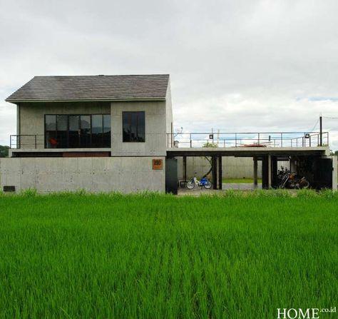 rumah itu tampak menonjol dengan beton ekspos abu-abu