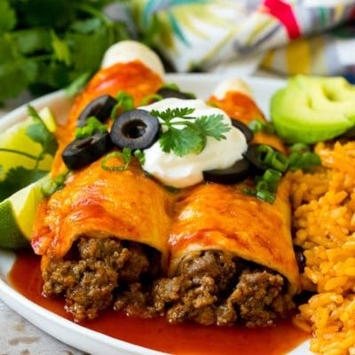 A Plate Of Beef Enchiladas Topped With Sour Cream Olives And Green Onions In 2020 Beef Enchilada Recipe Beef Enchiladas Enchilada Recipes