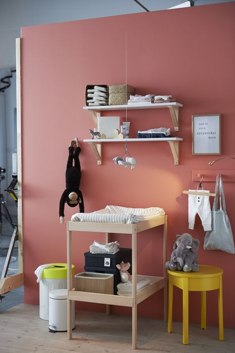 A nursery with changing table and crib in beech and storage in white