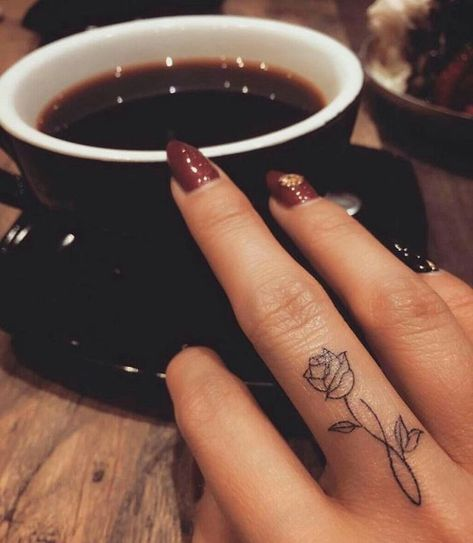 Blumen Tattoo am Mittelfinger, kleine Rose, dunkelroter Nagellack mit Steinen, Tasse Kaffee