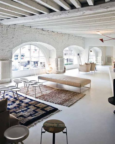 White, industrial, warehouse living. The huge arched windows are amazing!