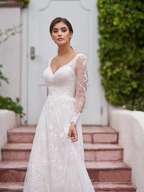 A gown that is fanciful yet sexy, style surfside from Simply Val Stefani was designed for the most elegant bride to be. Embroidered floral lace appliques adorn this A-line gown while long illusion sleeves hug your arms in the most flattering manner. A deep v-neckline sits on the fitted bodice for a sultry and charming touch. #laceweddingdress #alineweddingdress #longsleeveweddingdress #elegantbride