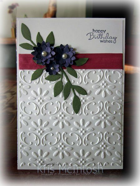 """Emboss  Whisper White card stock w Finial Press Embossing Folder, Rose Red 1/2″ Seam Binding,Stamp """"happy birthday wishes"""" Petite Pairs stamp set  Elegant Eggplant ink,leaves Always Artichoke card stock use the Little Leaves Sizzlit and attach them over the ribbon on the left hand side.Punch two sets of flowers from Elegant Eggplant card stock using the Boho Blossom punch.Attach the flowers to each other and to the card front using Mini Glue Dots add some Basic Pearls."""