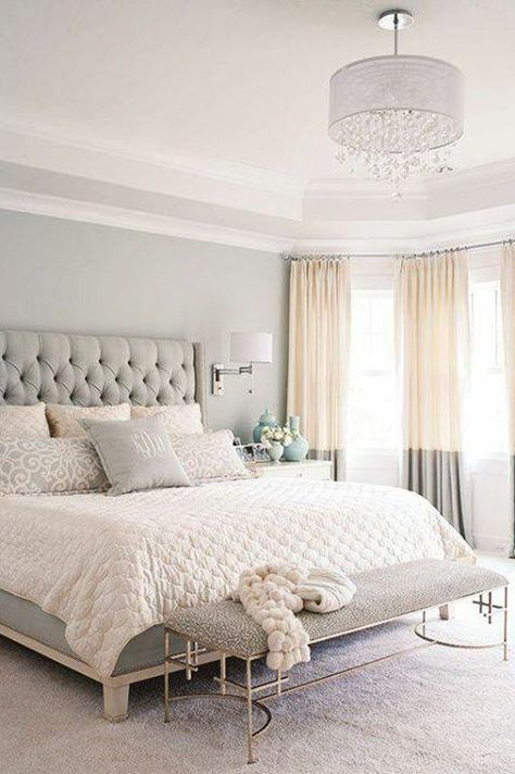Neutral bedroom with tall tufted upholstered gray headboard and bed frame, pale pink sheets and quilt, light gray metal base bench at the foot of the bed, silver wall sconces with white mini lamp shades and bi-color gray and cream floor to ceiling curtains, all decorated in a classic, feminine, traditional and glamorous interior design style.