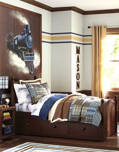 Boys train themed bedroom from Pottery Barn. The walls set the tone with an oversized mural and horizontal stripes that evoke a train track; a rug with a striped border echoes the decorative painting. Train-print sheeting is complemented by versatile brown-and-blue plaids, and furniture with a rich espresso finish gives the room a classic appeal.