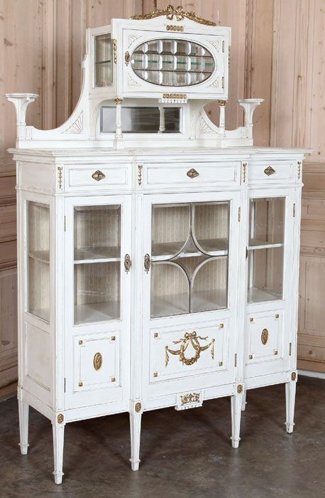 This stunning triple vitrine, set upon tapered and fluted legs, is fitted with beveled glass for display of your finest collectibles and cherished family heirlooms. Highlighted with carved floral wreath, swags and rosettes finished in gold, it features a raised demi cabinet flanked by two candle shelf pedestals overlooking a display surface.