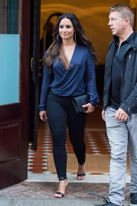 Demi Lovato wearing Gianvito Rossi Portofino Sandals, Saint Laurent Kate Monogram Clutch, J Brand 811 Photo Ready Mid-Rise Skinny Jeans in Bluebird, L'agence Gia Blouse in Navy and Mattia Cielo Diamond Studded Hoop Earrings
