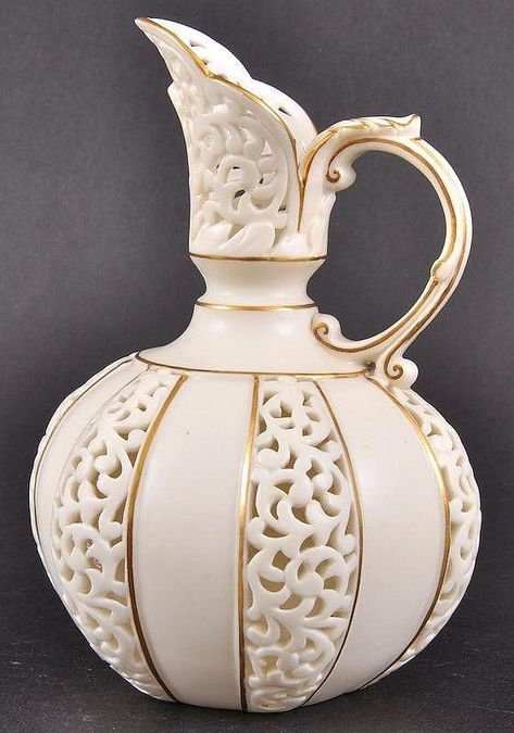A Royal China Works Royal Worcester blush ivory jug with pierced foliate decoration to the body, reticulated panels in the body and spout