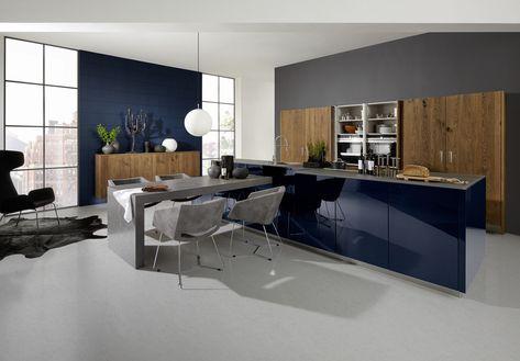 Blauwe, hoogglans keuken met houttinten. De kolomkasten van deze moderne keuken zijn opgebouwd in donkere houttinten, ook wel genaamd 'Real Oak'-deuren. Deze maken een mooie combinatie met het kookeiland, waarvan de keukenkasten in hoogglans zijn opgebouwd in een donkerblauwe kleur. De keukentafel sluit aan op het kookeiland en heeft dezelfde donkergrijze kleur als het werkblad.