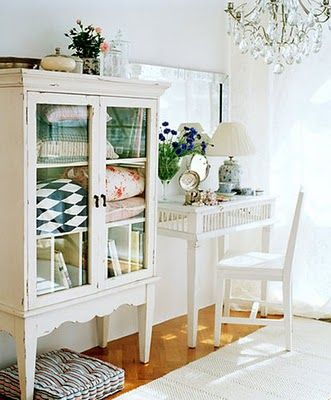 I love this vintage white cabinet used for linen and quilt storage