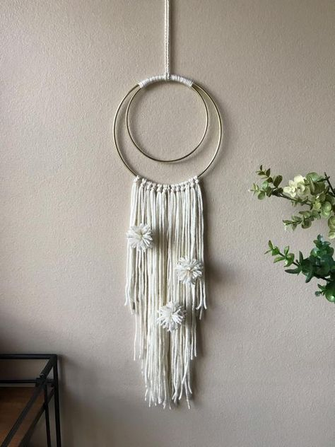 "This 2 hoop piece is on gold hoops, with a soft cream color for the strings and handmade Pom poms. It's neutral colors make it the perfect touch to any room in the house, as holiday decorations, or party decorations! (On an 8"" and 6"" hoop)"