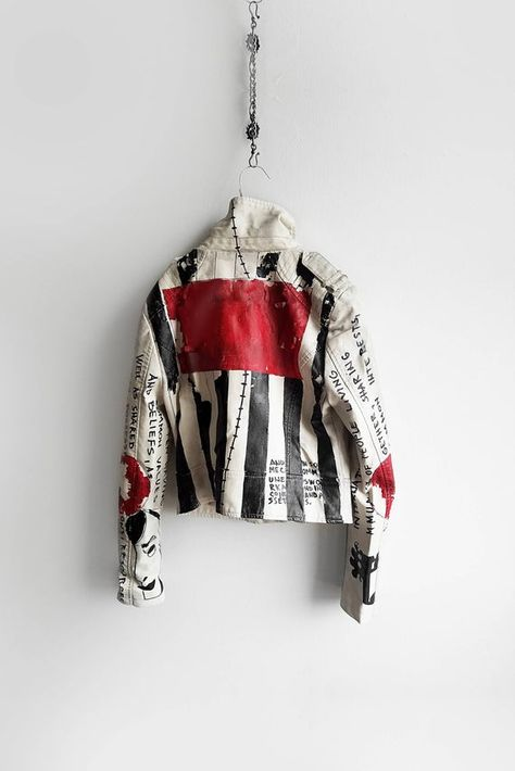 Commune hand painted off white jacket: Hand painted in black stripes and red patches. The entire jacket has been paint 'washed' to achieve the aged effect, plus the intentional small peal of the paint. There are two drawings on the bottom of the sleeves and random words defining 'commune'.  Each