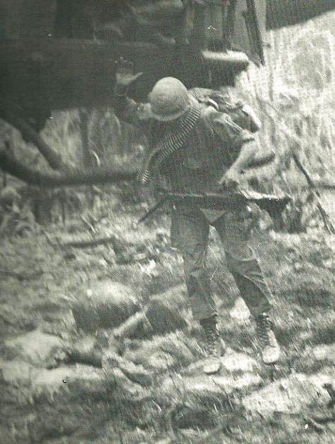 A soldier carrying an M60 and a bandolier of ammo jumps from a chopper.