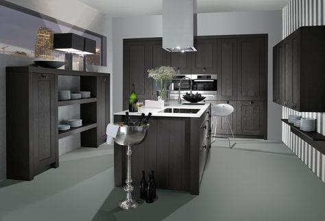 Prachtige, landelijk keuken met aan elke muur een ander soort keukenkast: planken, kolomkasten en zwevende kasten. Het kookeiland vormt het middelpunt van de keuken, temeer door de keuze van de rechthoekige dampkap.