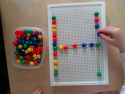 Making an H on the peg board with pegs and elastic bands (like a geo board)