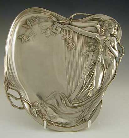 Manufacturer: WMF. Designer: unknown. Description: Polished pewter business card tray with art nouveau maiden & harp decoration. Country of Manufacture: Germany. Date: c.1906