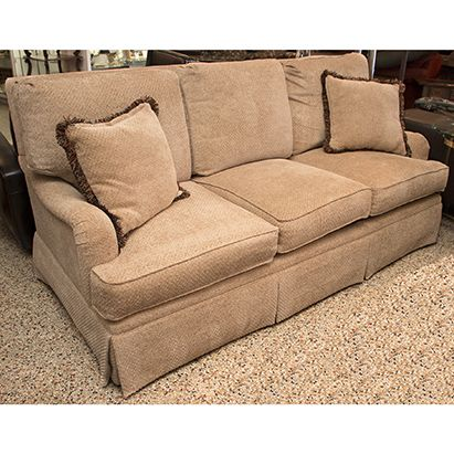 high end henredon sofa featuring classic english arms a kickpleat skirt and detached back and seat cushions upholstered in neutral waffle weaveu2026