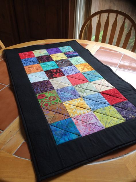 Batik Beauty quilted table runner - 20.5 x 35  This table runner is constructed with 32 4 squares. The squares are an assortment of gorgeous jewel tone batiks - all quilt shop quality! 32 different colors and designs. This runner would be great to display on your table throughout the entire year. The border is a black batik. The back of the runner is solid black. This runner could also be hung on the wall as a beautiful quilted tapestry.  The runner measures approximately 20.5 x 35. It is…