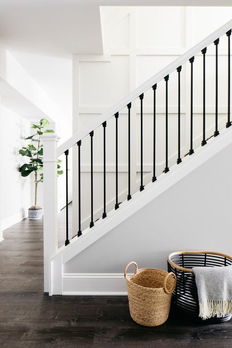 Staircase bright and beautiful for a basement build-out. Black and White Herringbone runner with white on white board paneling. Black metal balusters and white handrails