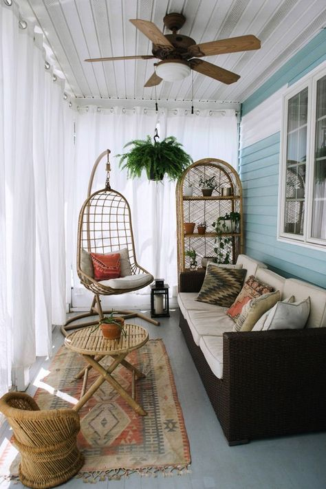 a small boho sunroom with a dark sofa, wicker furniture and a hanging chair plus… - Home Decoration Small Sunroom, Small Balcony Decor, Small Enclosed Porch, Conservatory Decor Small, Outdoor Curtains, Outdoor Chairs, Sunroom Curtains, Front Porch Curtains, White Curtains