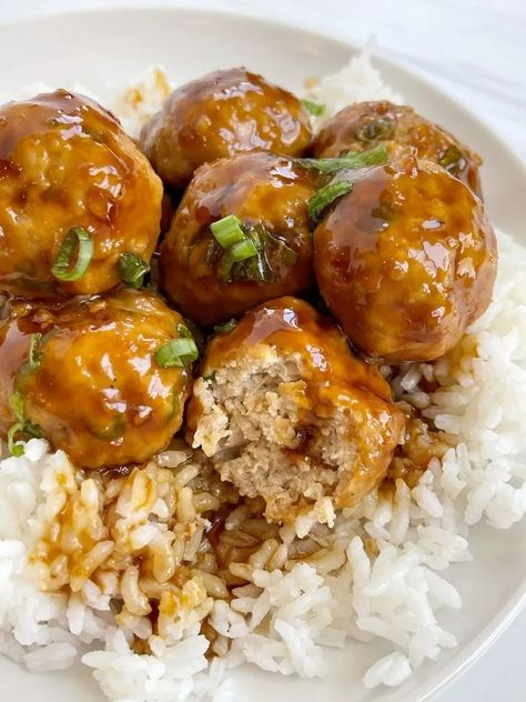 A plate with white rice on it and ground chicken pineapple teriyaki meatballs garnished with green onion.