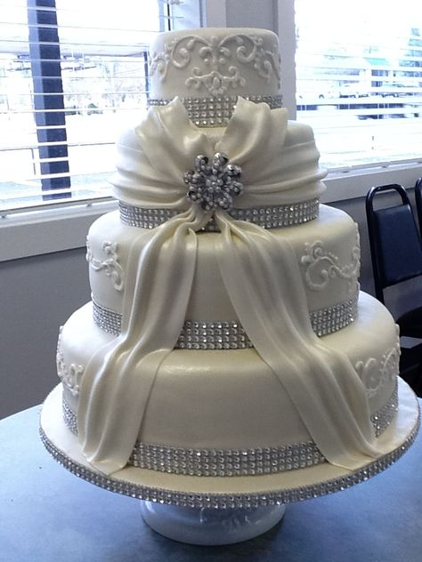 4 tier white wedding cake with scrools & flowing bow with brooch--by Tracy Martin@ Simply Southern Specialties.
